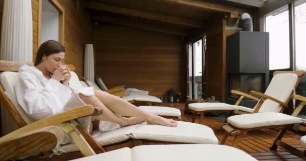 eine schöne Frau im weißen Bademantel und trinkt heißen Tee oder Kräutertee mit Blick nach draußen. die Frau entspannt sich und denkt, während sie nach draußen schaut.