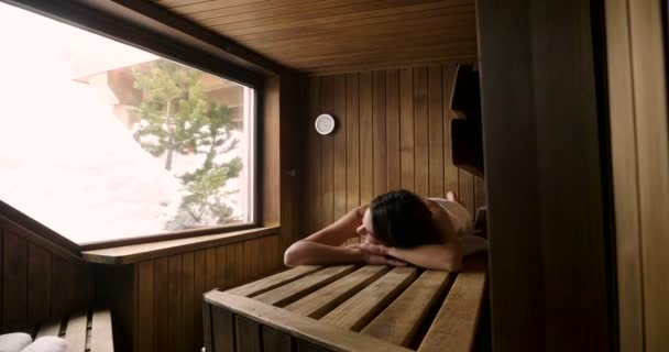 Eine schöne Frau mit einem weißen Handtuch geht in die Sauna: Die Sauna besteht aus Holz mit einem großen Fenster mit Blick auf den Schnee. Konzept von: Entspannung, Urlaub, Wellness-Center.