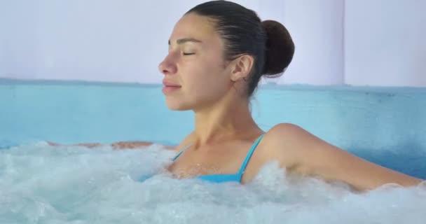 Krásná mladá dívka (žena) odpočíval v hydromasážní vana, v modrých plavkách, na modrém pozadí. Pořadatel: léčebné procedury, masáže těla, spa smetana, klid, voda procedurami, bazén