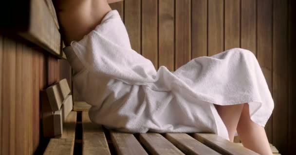 Krásná žena na sobě bílý ručník trvá sauna: sauna je vyroben ze dřeva s velkým oknem s výhledem na sněhu. Koncept: relax, dovolená, wellness centrum.