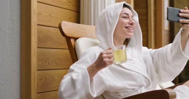 Krásná žena v centru, oblečený v bílém županu, pije horký bylinkový čaj a vyfotí poslat přátelům. Koncept: technologie, klídek, sociální sítě.