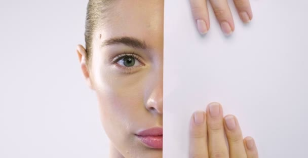 Close up of the face of a beautiful girl with perfect skin and clean all impurities and puts a white sheet on half face to hide the impurities. Concept of beauty secrets and creams.
