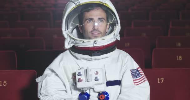 Ein Astronaut schaut sich einen Film im Kino an und genießt ihn. Konzept: Kino- und Weltraumfilme, Film aus der anderen Welt, surreale Situationen.