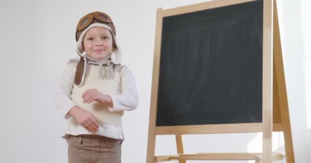 video z holčičky oblečený jako pilotní stojí na tabuli s náručí překřížené a usmívá se
