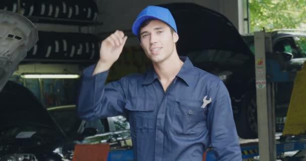 In einer Werkstatt lächelt ein Mechaniker, nachdem er Öl und Motor am Auto überprüft hat, weil das Auto erfolgreich repariert wurde. Konzept von: Sicherheit, Sicherheit, Versicherung und Unterstützung