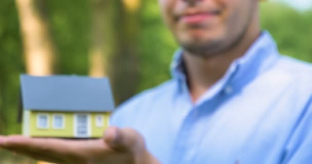 Realtor, broker, businessman is holding a small yellow house for sale, buying or renting real estate, a hand, a blue shirt on a nature background. Concept purchase of a new house, sale of real estate.