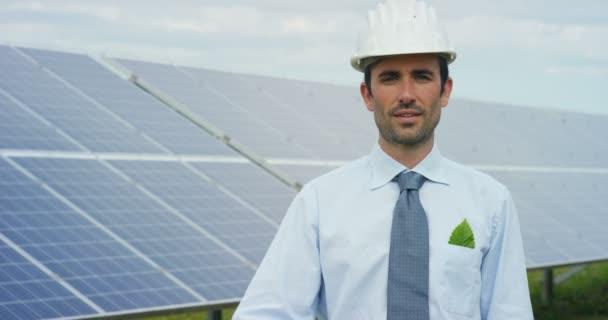 zpomalené video člověka ukazuje na kameru žárovku a stojící na eco solárních panelů, střecha buňky sluneční soustavy stanice