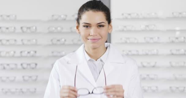 zpomalené bruneta žena uprostřed optické brýle, při pohledu na fotoaparát a usmívá se rukama přes