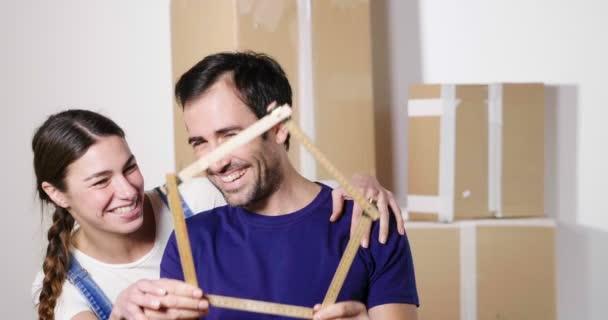 Portrét pár v lásce, který právě koupil dům a je v pohybu. Nevěsta a ženich úsměv a držte metr ve tvaru domu v jejich rukou. Koncept: budoucnost, rodinu, hypotéky a půjčky.