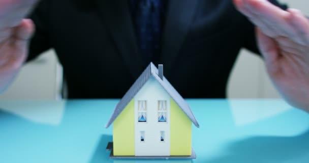 Versicherung von Feuer und Diebstahl ...die Hände von einem Versicherer oder Makler zeigt ein Haus mit Grundriss und Dokumente mit gesicherten Hausschlüssel. Konzept der Heimat, Familie, Versicherung. Haus mieten