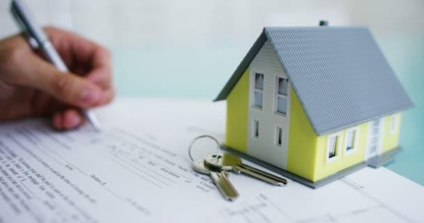 pojištění požáru a krádeži .the rukou pojistitele nebo realitní agent dům s půdorys a dokumenty s garantovaného domu. koncept domova, rodiny, pojištění. Pronájem domu