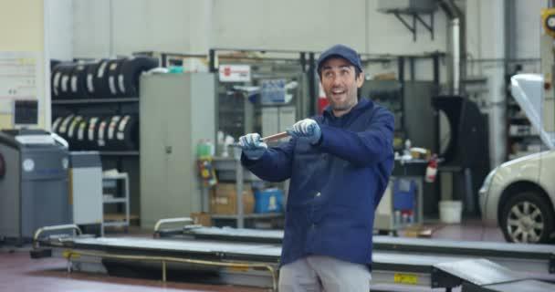 Veselý mladý automechanik v autoservisu, bavit a tančit s klíčem. Koncepce: opravy automobilů, diagnostiku, opravy specialista, technické služby a palubní počítač, doby přestávky.