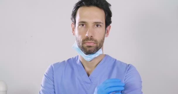 handsome Caucasian doctor, man standing against grey background with arms crossed, video