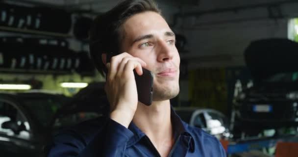 V správce mechanik používá telefon reagovat na zprávy zákazníka a volá jako auto zákazníka. Koncept: záruka, bezpečnost, pojištění a pomoci, Recenze, technika a péče o zákazníka.