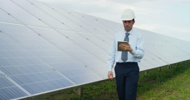 zpomalené video člověka drží digitální tabletu, chůzi a kontrolu v solární panely systému stanice venku