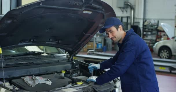 Specialista automechanik v autoservisu, zkontroluje auto, motor, motor, karburátor. Koncepce: opravy strojů, diagnostika závad, specialista na opravy, technická údržba a palubní počítač.