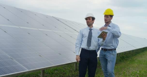 zpomalené video dvou mužů chodí na solární panely a mluví, muž držící digitální tabletu a diskuse