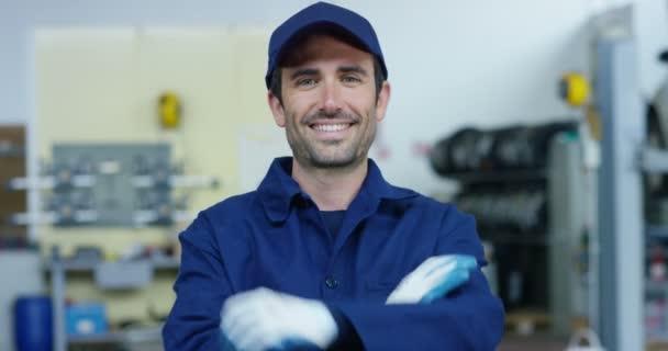Portrét mladého krásného automobilového mechanika v automobilové dílně, v zázemí servisu. Koncepce: opravy strojů, diagnostika závad, specialista na opravy, technická údržba a palubní počítač