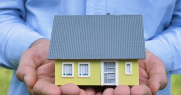 Realitní makléř, obchodník drží malý žlutý dům na prodej, koupi či pronájem nemovitostí, ruka, modrou košili na pozadí přírody. Koncept nákupu nového domu, prodej nemovitostí.