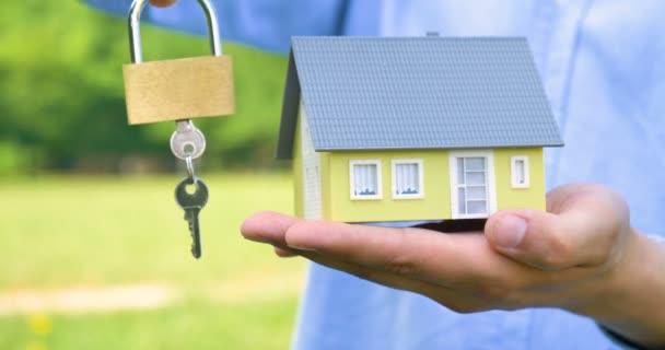 video o osobě držící klíče v modelu zámku a v domovní hračce