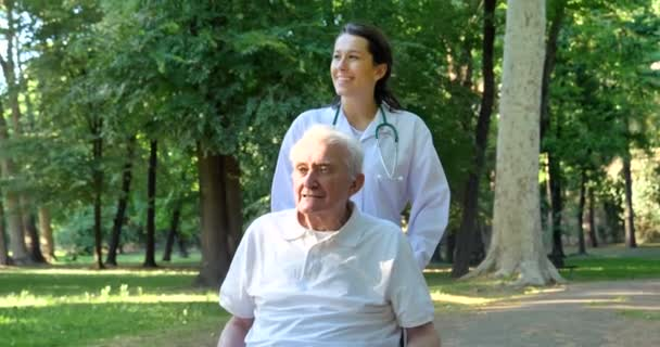 video of caregiver nurse with pensioner man in wheelchair, summer park