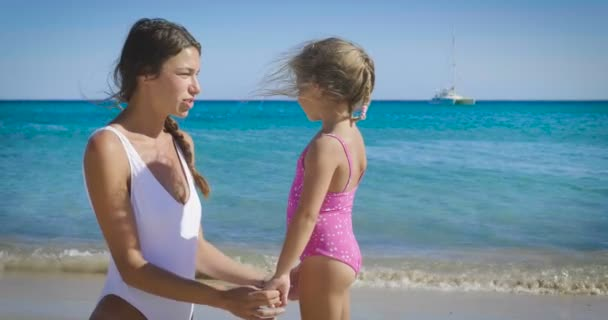 The best moments, the mother with a little daughter are played on the sea, in sunglasses, in swimsuit, sun protection cream, sea and sand background. Concept: love, lifestyle, children, vacations