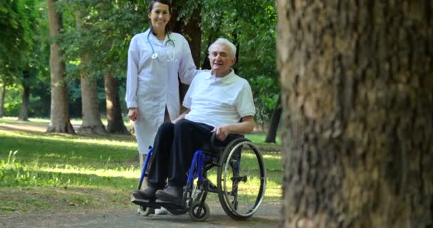 video of caregiver nurse with pensioner man outdoors in park posing on camera, man in wheelchair