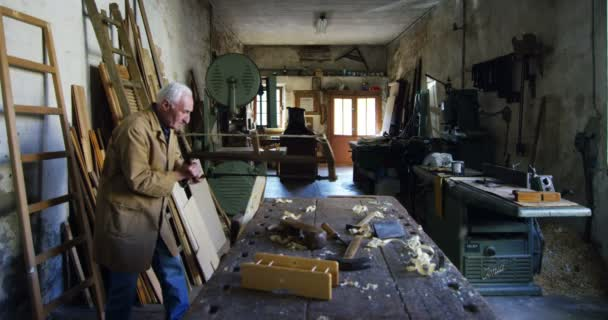 in an old carpentry an elder is working the wood with traditional tools such as planer and saw
