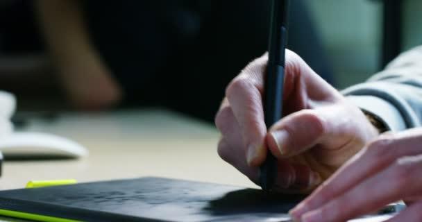 video, ruce grafického návrháře grafiky kreslené na grafickém tabletu v pomalém pohybu