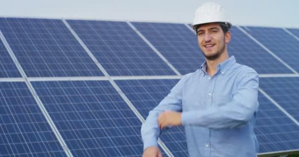 Kaukázusi üzleti ember állt eco solar panelek karját keresztbe és látszó-on fényképezőgép, videó