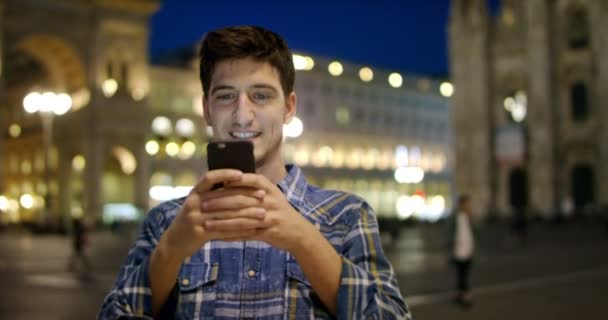 Man look at night in city. Milan italy Handsome young business man using telephone smiling happy wearing wearing blue shirt. Urban male. sms texting man using phone in urban city app