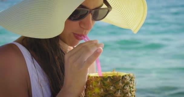 video of woman enjoying pineapple juice on sandy beach