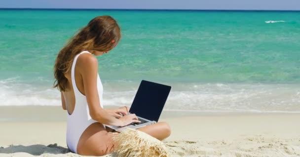 lassított videót a nő ül a strandon, és használ laptop