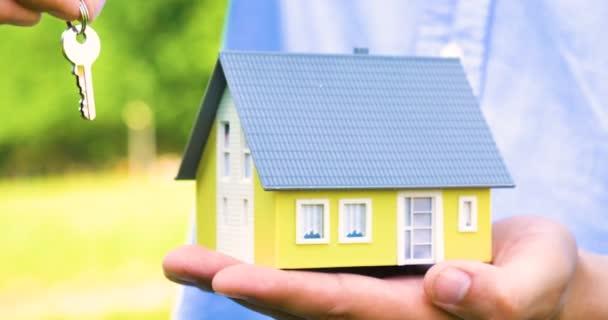 Realitní makléř, obchodník drží malý žlutý dům s klíči a zámek, na prodej, nákup, ochrana, pronájem nemovitostí, ruku, modré tričko, venkovní. Koncepce: domácí ochrana, alarm systém.