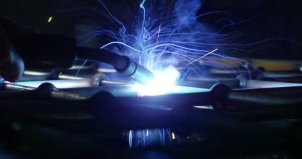 .Kováře nebo svářeč, s jeho svářeč, svařování oceli a železa, v extrémně pomalém pohybu. Svářečka používá masku k ochraně zraku před jiskrami. koncept: manuální práce, průmysl, kovář, svářeč