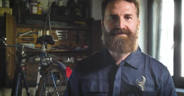 Portrait handsome Caucasian bearded man in workshop, posing and looking at camera with arms crossed