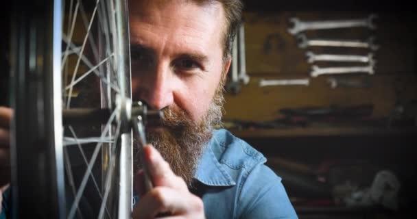 video of bearded Caucasian man repairing bicycle wheel