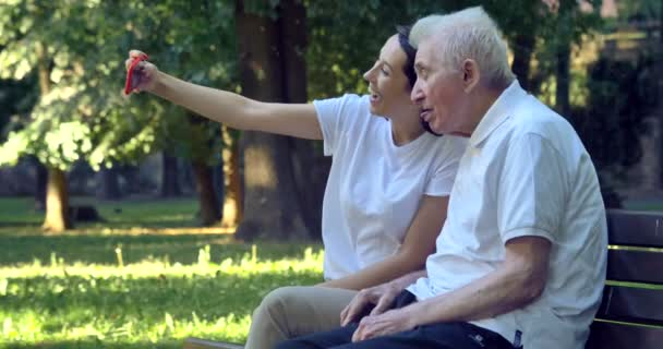 video of caregiver nurse with pensioner man smiling on mobile camera and taking selfie