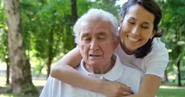 video of caregiver nurse hugging pensioner man in park