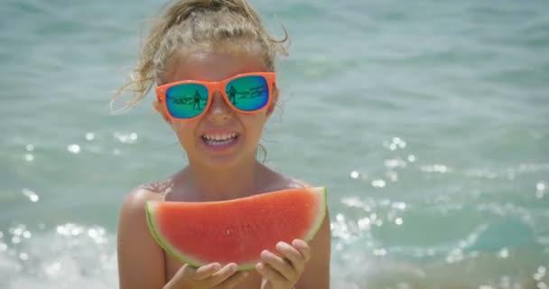 ein kleines Mädchen isst die Wassermelone am Strand, um sich abzukühlen und im Hintergrund sieht man das Meer