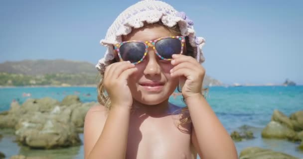 Portrait of beautiful little girl having fun on the sea, cute smiling in panama, sun protection cream, background of sea blue water and rocks. Concept: children, childhood, summer, freedom, kids, baby