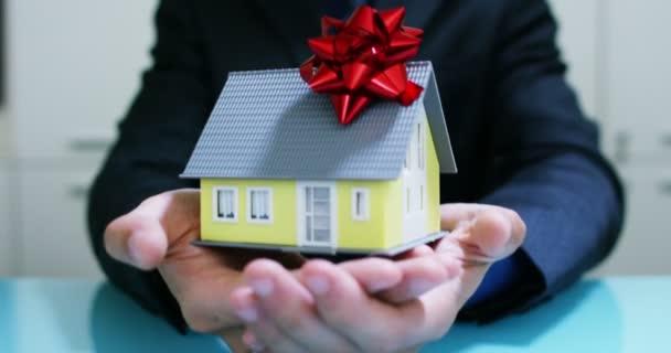 pronajmout nebo koupit dům .the rukou pojistitele nebo realitní agent ukazuje dům s klíče od domu.