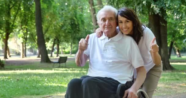 videó a gondozó nővér ölelve nyugdíjas ember a parkban, és mosolyogva a kamera
