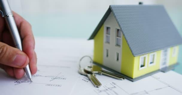tűz- és lopás .a kezében egy biztosító vagy ingatlanügynök mutatja a ház alaprajzát és okiratok-val biztosította lakáskulcsokat biztosítás .