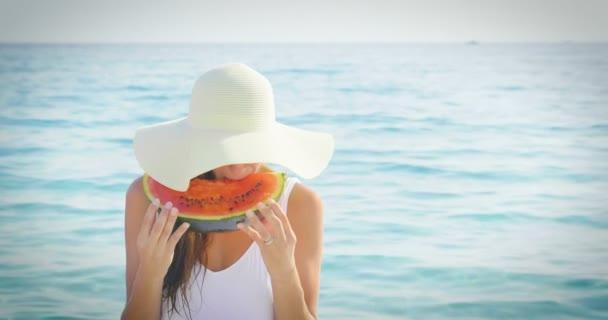 videó a nő kalapot és napszemüveget eszik friss édes görögdinnye szelet, kék tengeren