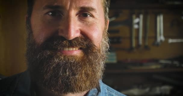 videozáznam hezkého kavkazského vousatého muže v dílně, pózovník a pohled na kameru s úsměvem