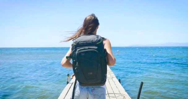 video of traveler woman with backpack on wooden pier