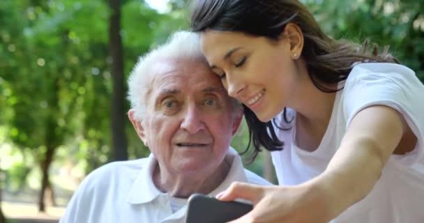 video of caregiver nurse with pensioner man making selfie on mobile phone