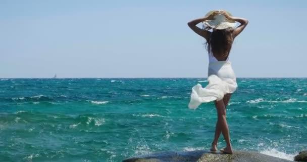 zadní pohled video krásná žena nosí bílé plavky a pareo a postavení na moři vody