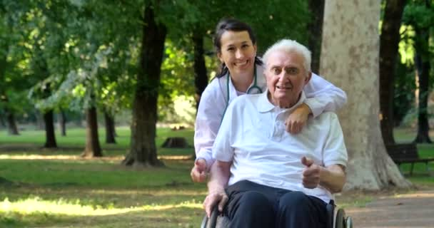 video of caregiver nurse with pensioner man gesturing thumbs up in park and looking at camera